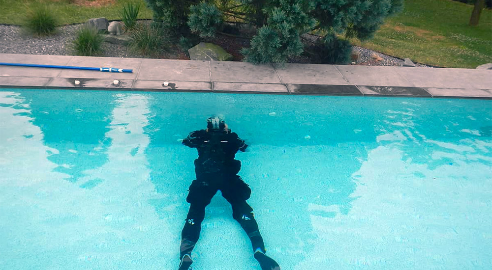 A man in a diving suit trying to find leak in the pool